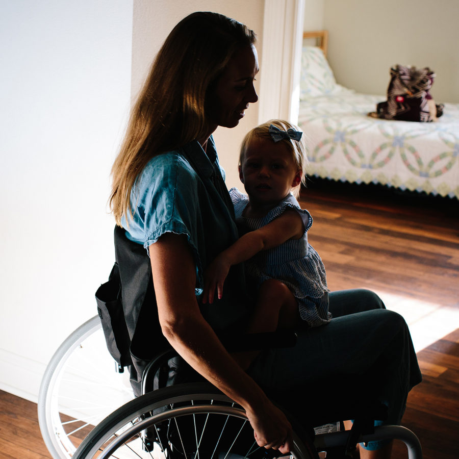 Sharon sitting in a wheelchair with her daughter on her lap.