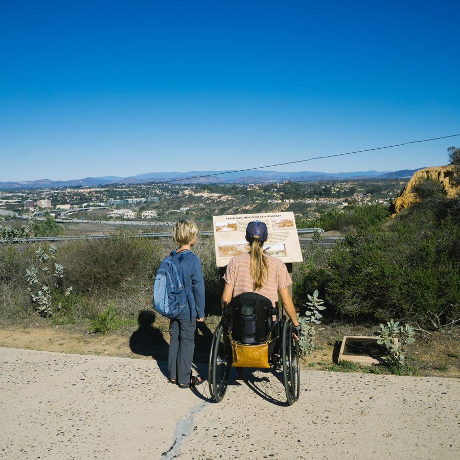Sharon on a paved trail in wheelchair with her son by her side looking at a sign at a viewpoint overlooking the valley